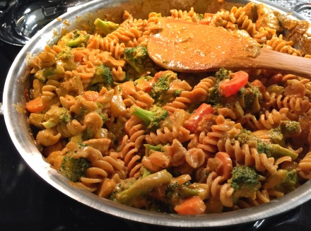 mixing pasta, sauce, and veggies